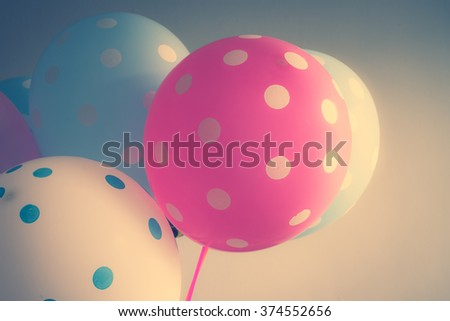 Colorful pokadot festive balloons on wall with retro filter effect - stock photo