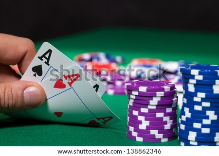 Colorful poker chips and two Ace closeup on green cloth - stock photo