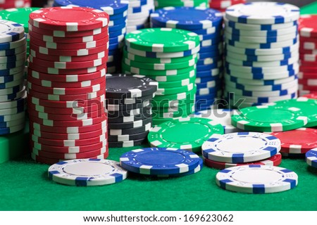 colorful poker chips on a green casino table - stock photo