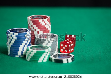 Colorful poker chips on green background with copy space - stock photo