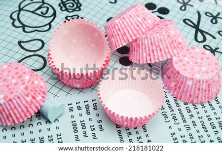 Colorful polka dot cupcake wrappers with color coordinated baking supplies. Close Up with shallow dof. - stock photo