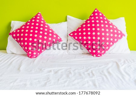 Colorful polka pillow on white bed - stock photo