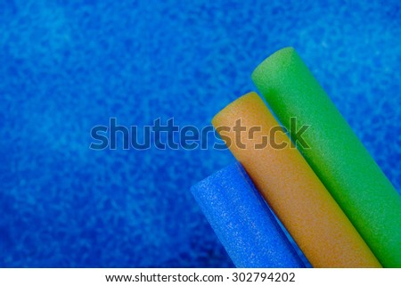 Colorful pool toy float tubes in a calm crystal clear and clean pool - stock photo