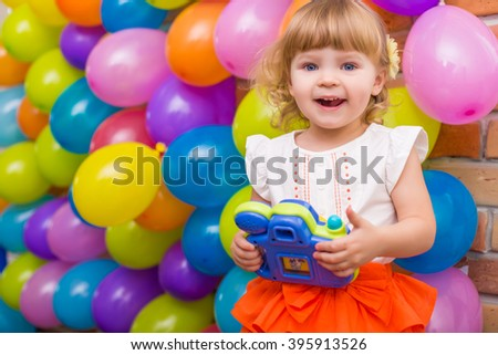 colorful portrait of cute adorable baby girl with balloons background and toy photo camera in her hands
