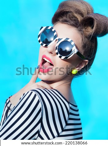 Colorful portrait of young attractive laughing woman wearing stripy sunglasses  - stock photo