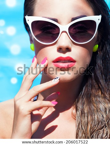 Colorful portrait of young attractive woman wearing sunglasses by the swimming pool, summer beauty and nail art concept