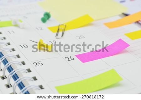 Colorful post It notes with pin and clip on business diary page - stock photo