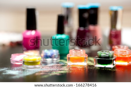 Colorful powder for nails on black background