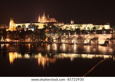 Colorful Prague gothic Castle above the River Vltava with Charles Bridge in the Night - stock photo