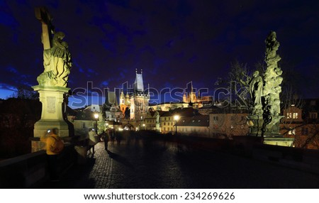 Colorful Prague gothic Castle with St. Nicholas' Cathedral and Bridge Tower from Charles Bridge above the River Vltava after Sunset, Czech Republic - stock photo