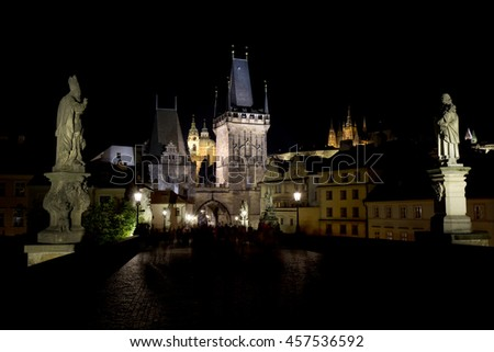 Colorful Prague gothic Castle with St. Nicholas' Cathedral and Bridge Tower from Charles Bridge above the River Vltava in the Night, Czech Republic - stock photo
