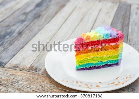 colorful rainbow cream cake on wood table - stock photo