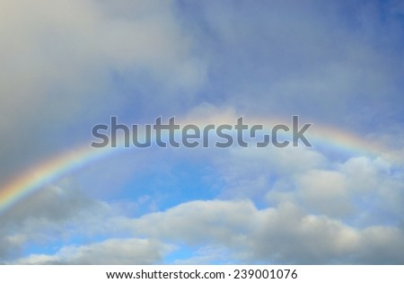 Colorful rainbow on blue sky and clouds - stock photo