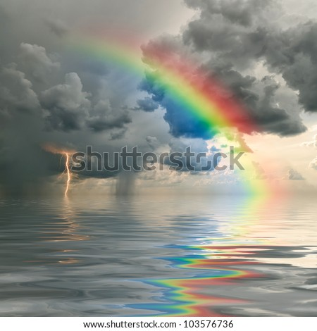 Colorful rainbow over ocean, thunderstorm with rain and lightning on background - stock photo