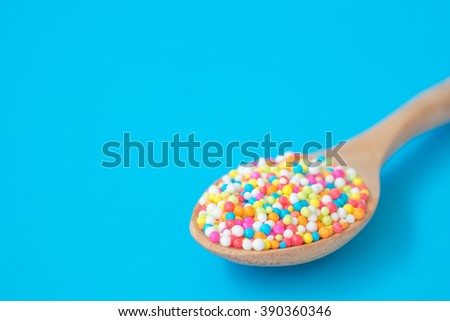 colorful rainbow sweet candies spreading pastry decoration on wooden spoon - stock photo