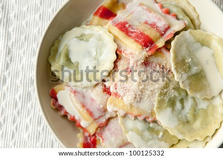 colorful ravioli pasta stuffed with spinach and cheese covered with a creamy garlic sauce and parmesan cheese - stock photo