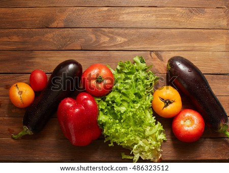 Colorful raw fresh vegetables on the old wooden background