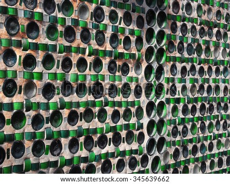 Colorful recycling background with texture of empty wine bottles in the wall - stock photo