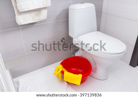 Colorful red basin, yellow gloves and cloth for cleaning in a bathroom standing on the floor alongside a plain white toilet - stock photo