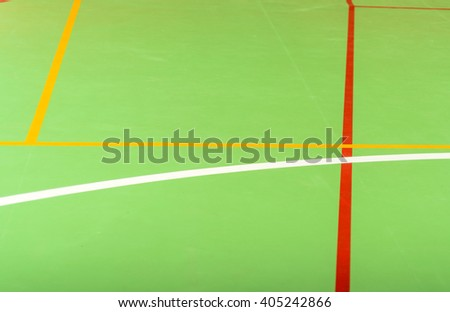 Colorful red, yellow and white markings on a green indoor sports court in an abstract background pattern ad texture