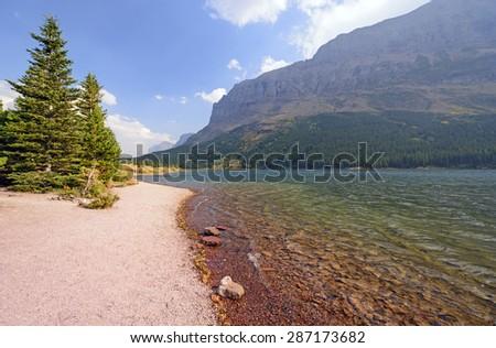 Colorful Redrock Lake in Glacier National Park in Montana - stock photo
