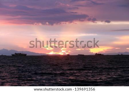 Colorful reflection of Manila bay sunset at the baywalk. - stock photo