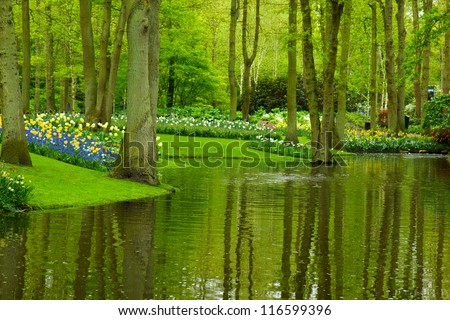 Colorful river and flowerbed  in dutch garden 'Keukenhof', Holland - stock photo