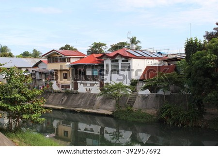 Colorful river bank with the townhouses, white houses with red roofs, green city houses, relaxing landscape of small town, summer in a town, red roof houses by the river, Philippines - stock photo