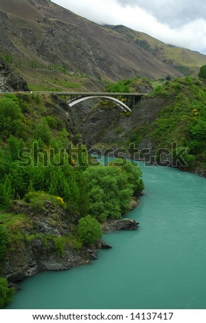 Colorful river with a beautiful bridge crossing it. - stock photo