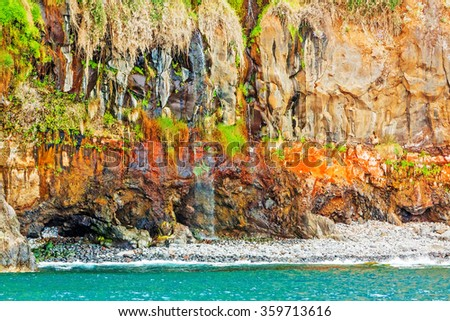Colorful rocky cliff coast of Madeira between Jardim do Mar and Calheta - stock photo
