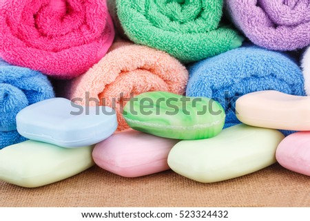 Colorful rolled towels with soaps closeup picture.