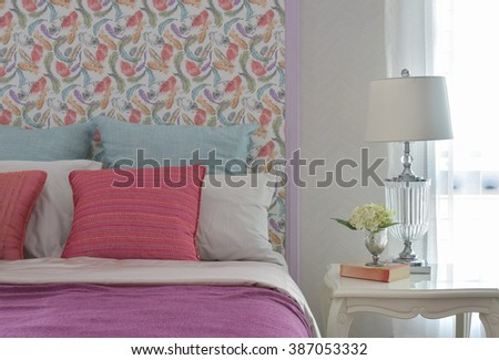 Colorful romantic bedding style with beautiful pattern headboard and crystal base reading lamp - stock photo