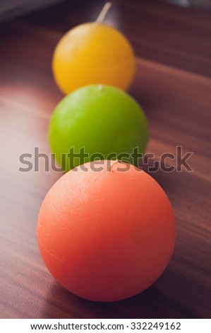 Colorful round candles,orange, green, yellow.