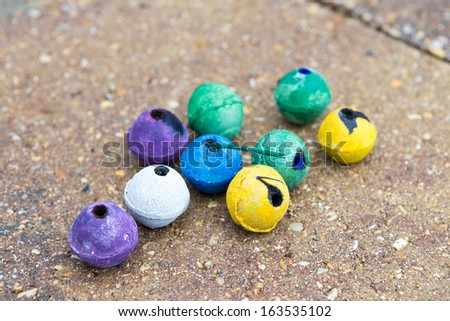 Colorful round smoke bombs naturally on the paved street some of them used some of them not. They have purple, green, yellow, white and blue colors, surely someone having fun - stock photo