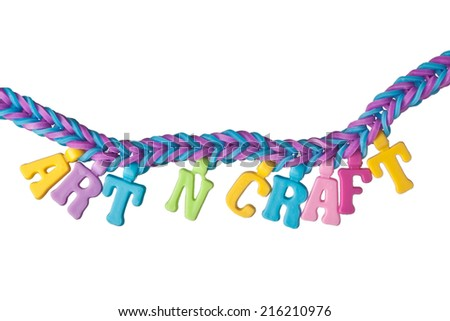 Colorful rubber band bracelet with the words ART N CRAFT isolated on white background  - stock photo
