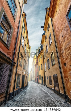 Colorful rustic Alley with Cobblestone road with a surrealistic feeling, Prastgatan, Stockholm - Sweden - stock photo