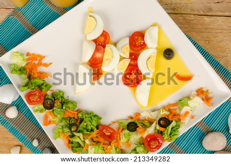 Colorful salad shaped as a fish, creative kid food - stock photo