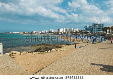 Colorful sandy beach with clean water on which are a lot of blue umbrellas and deck chairs. Incidental people are swimming and sunbathing, with white buildings on a background, Protaras in Cyprus