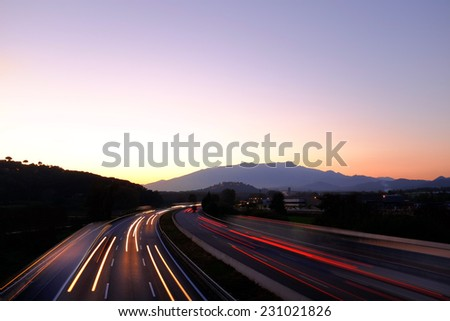 Colorful scene of moving vehicles on busy highway at dawn leaving beams of red lights.  - stock photo