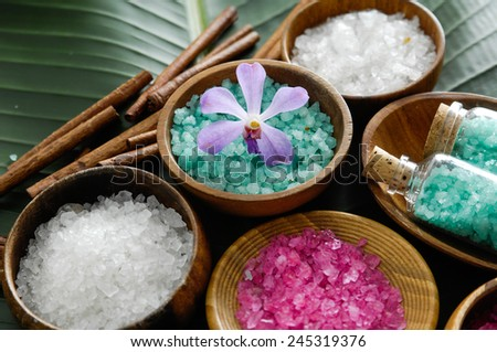 colorful sea salt in wooden bowl with orchid on banana leaf  - stock photo