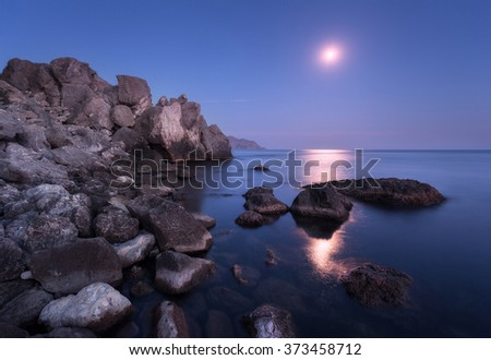 Colorful seascape with moon and lunar path with rocks at night in summer. Mountain landscape at the sea