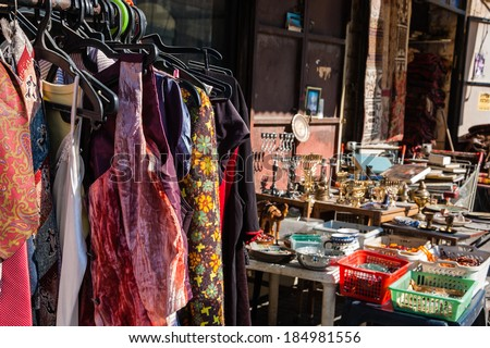 Colorful secondhand vintage clothes,  judaica objects and other Israeli souvenirs at the flea market in Jaffa (Israel). Selective focus on the dresses. - stock photo