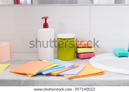 Colorful set of household cleaning cloths spread out alongside the hand basin in a bathroom with sponges and soap behind - stock photo