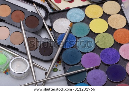 Colorful set of professional palette of eyeshadow red orange green violet pink yellow purple black beige brown colors foundation powder and make-up brushes on white background, horizontal picture - stock photo
