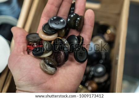 colorful sewing buttons in the hands, selection of the right buttons