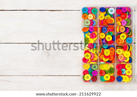 Colorful sewing buttons on a wooden background - stock photo