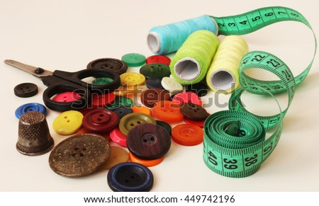 colorful sewing buttons, thread , scissors, thimble and measuring tape tailor on wooden background