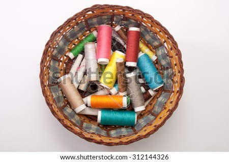 Colorful sewing thread in a wicker basket.