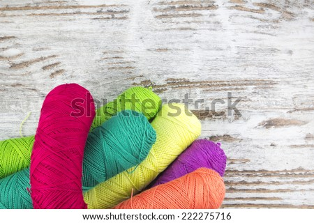 Colorful sewing threads in a wood background - stock photo