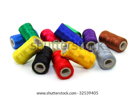 Colorful sewing threads on white background - stock photo